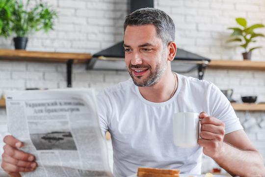 Mann, der beim Frühstück eine Zeitung liest